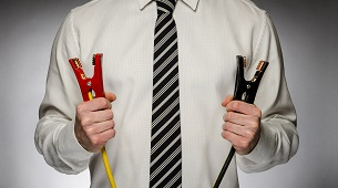 Man wearing tie holding jumper cables