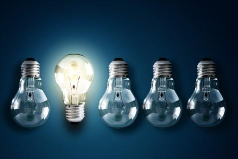 Illuminated light bulb in a row of dim ones concept for creativi